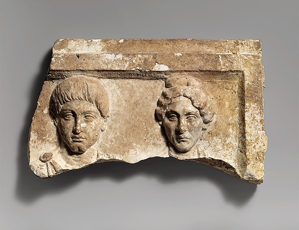 Top of a marble funerary relief with portrait busts of a young man and an elderly woman